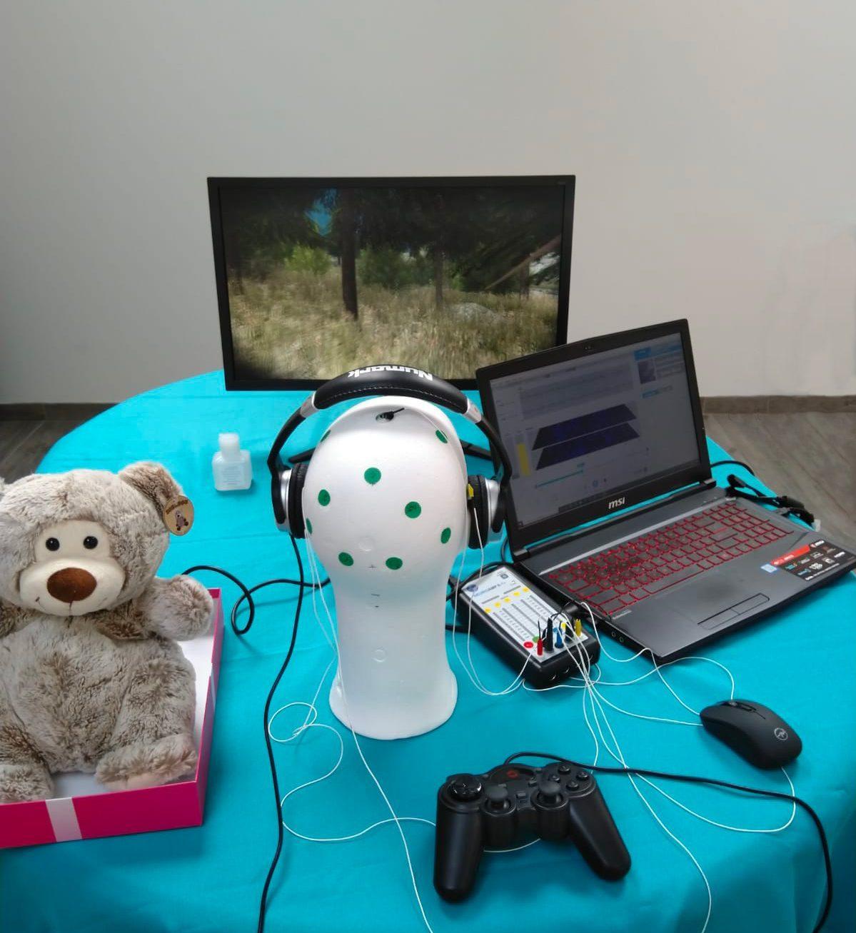 Matériel de Neurofeedback complet. Il y a un ours en peluche, une tête de mannequin en polystyrène, un amplificateur d'EEG, une manette de jeu vidéo, un ordinateur portable avec sa souris et un écran en arrière plan
